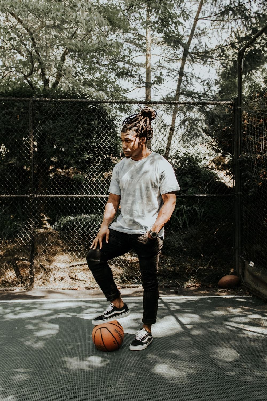 man stepping on brown basketball