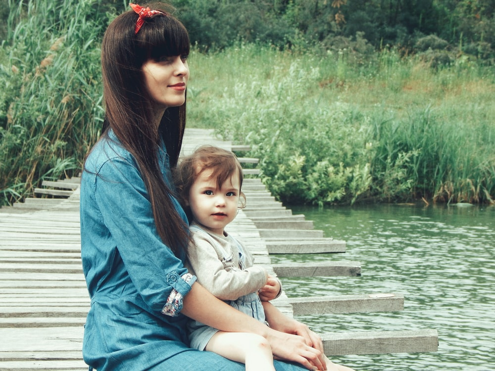woman holding her child on dock near body of water