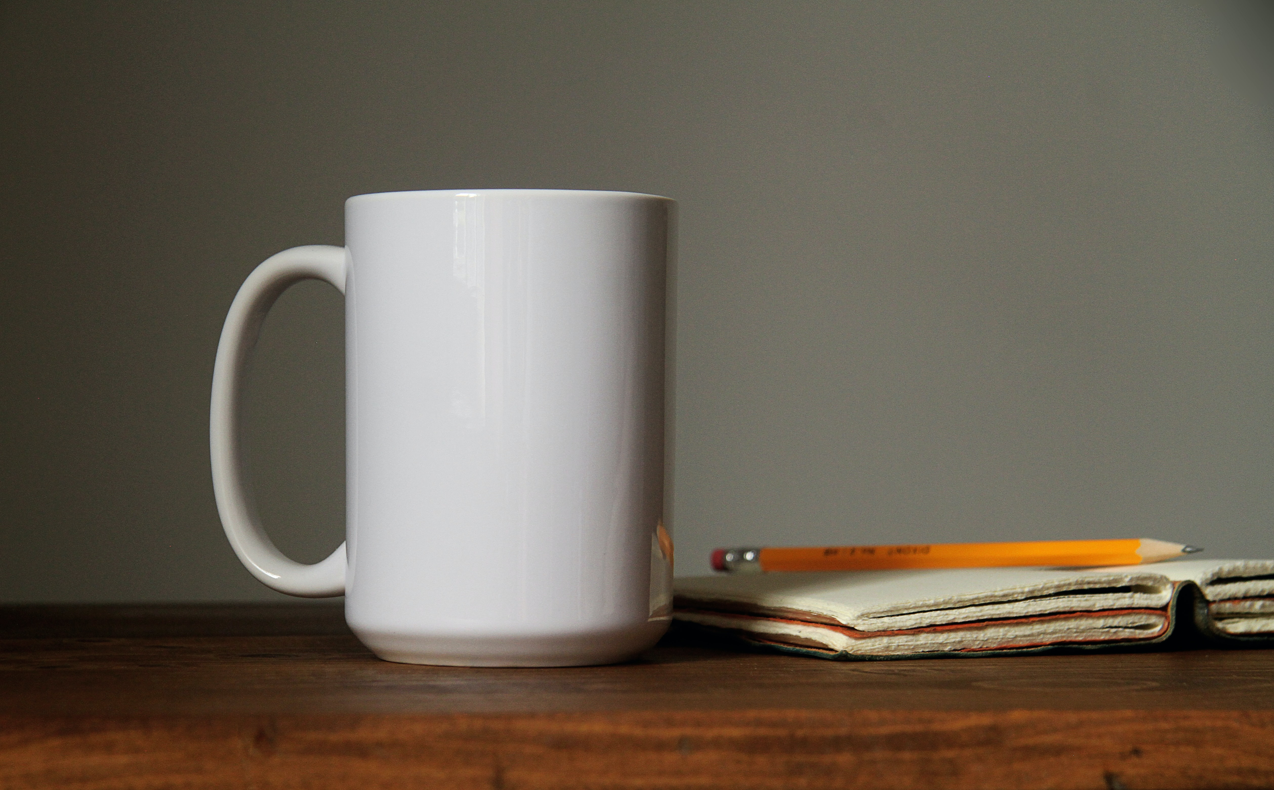 white ceramic mug beside orange pencil on open book page