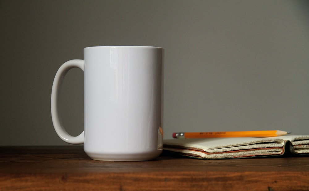 white ceramic mug beside orange pencil on open book page