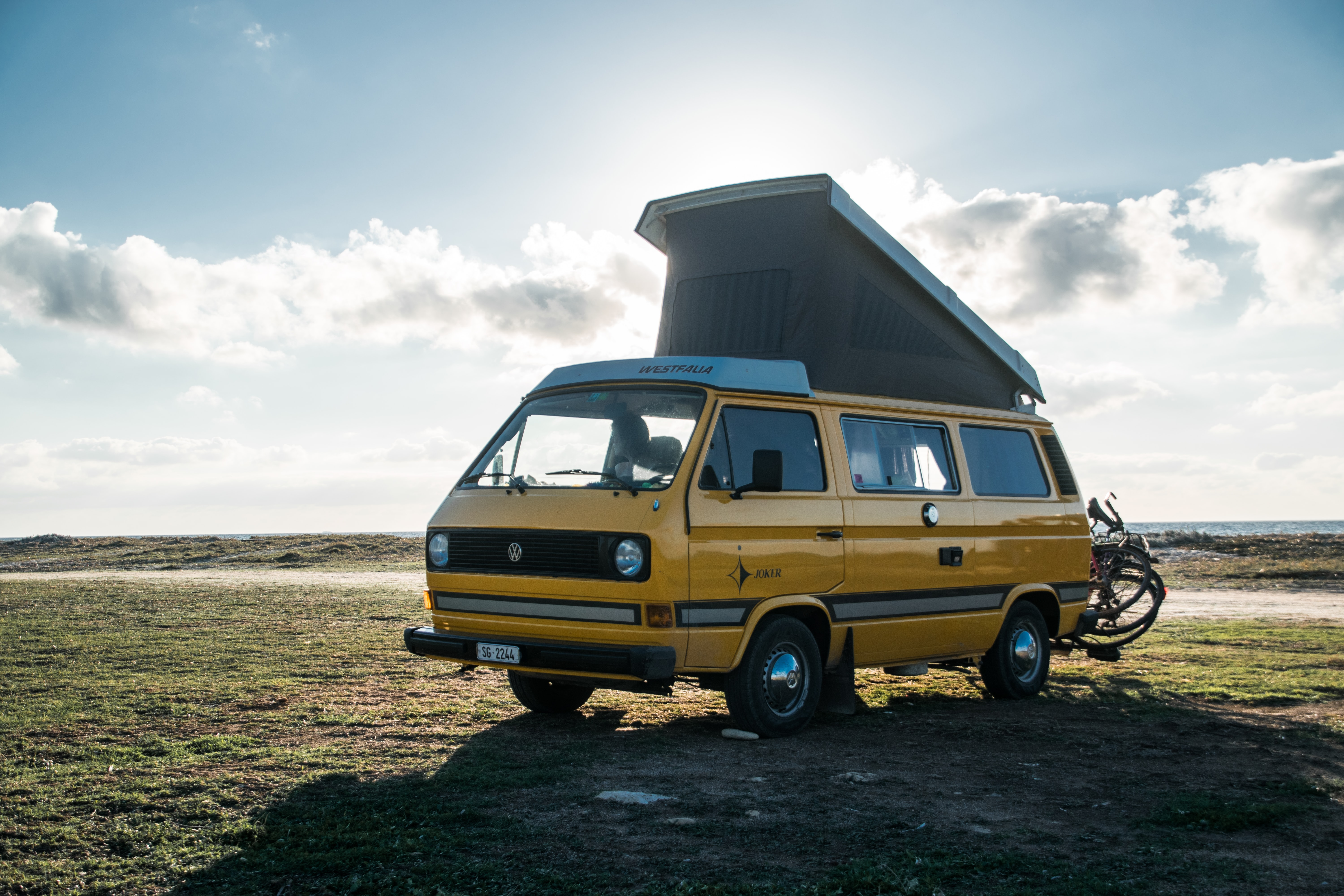 yellow Renault van parked on green grass at daytime