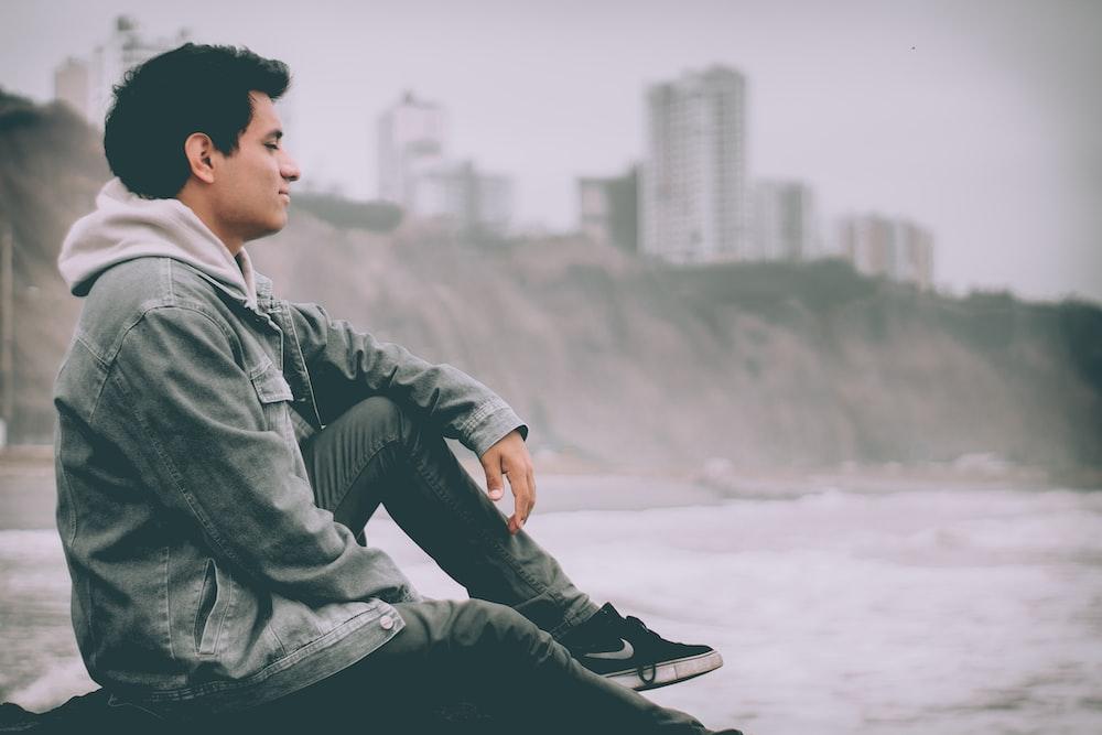 man sitting near body of water during daytime
