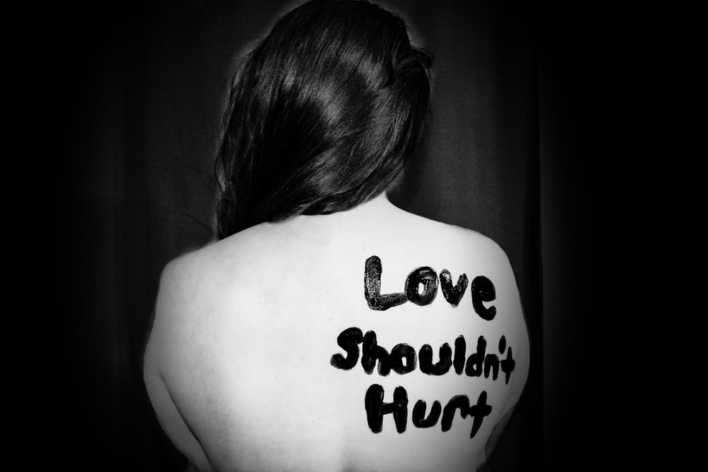 love shouldn't hurt-printed on back of woman
