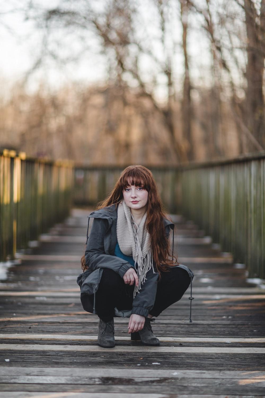 woman sitting on wooden bridge