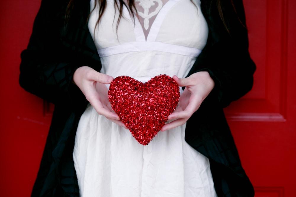 women holding red heart pillow