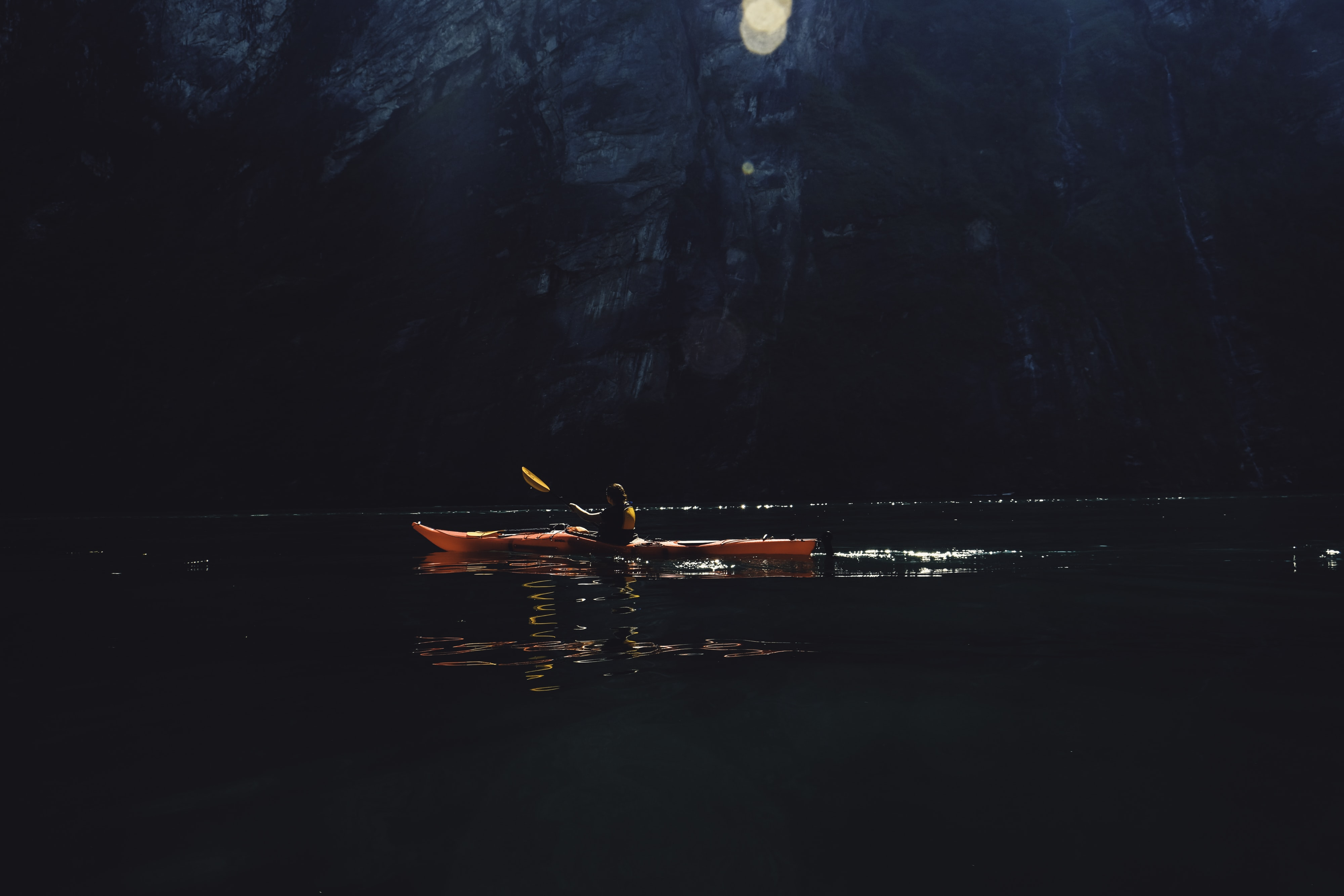person riding on red kayak while paddling on body of water