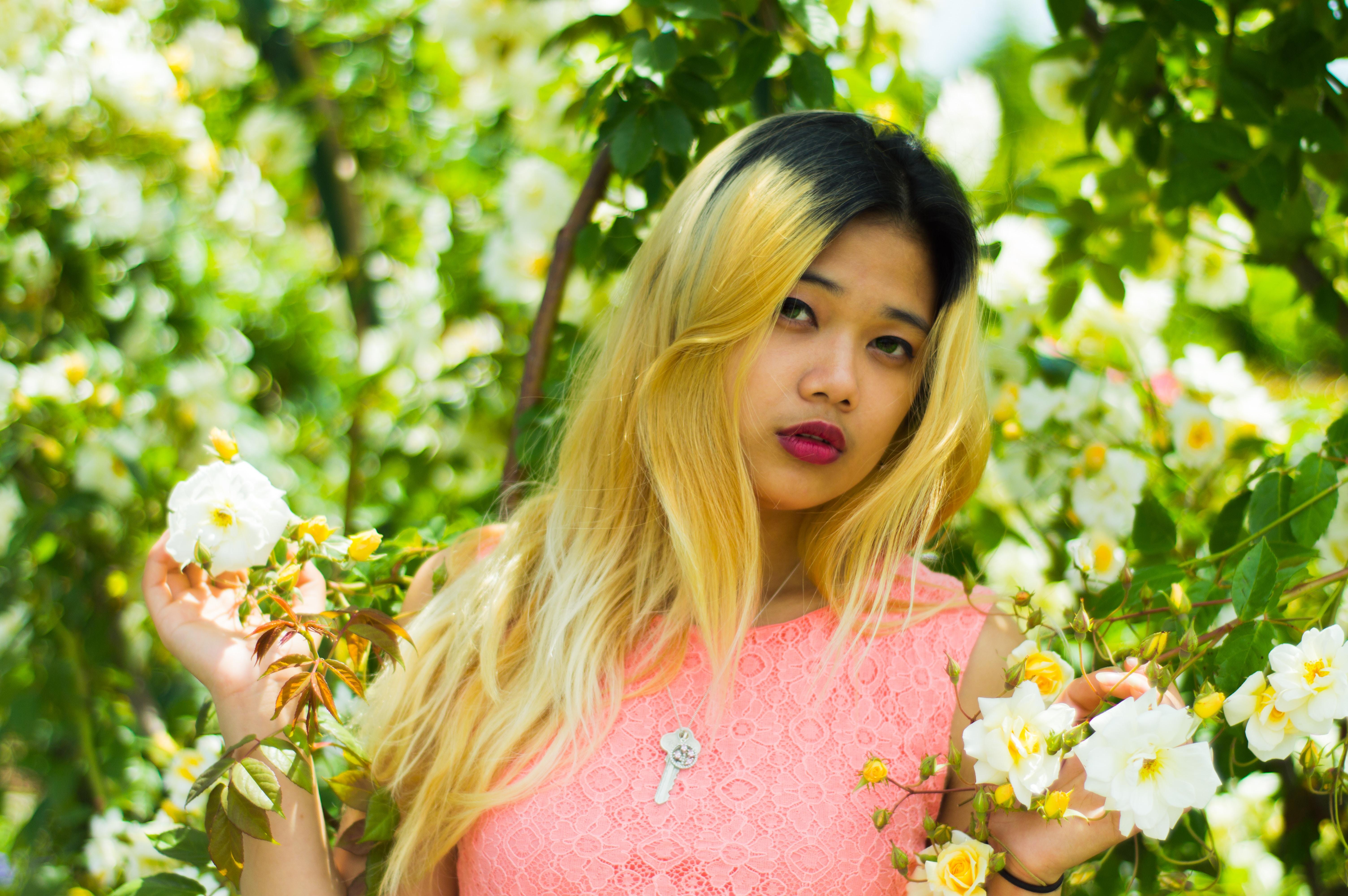 woman standing between white petaled flower