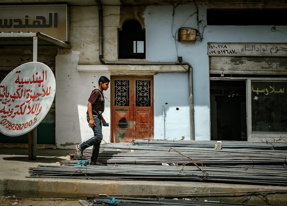 boy walking on metal frame beside building