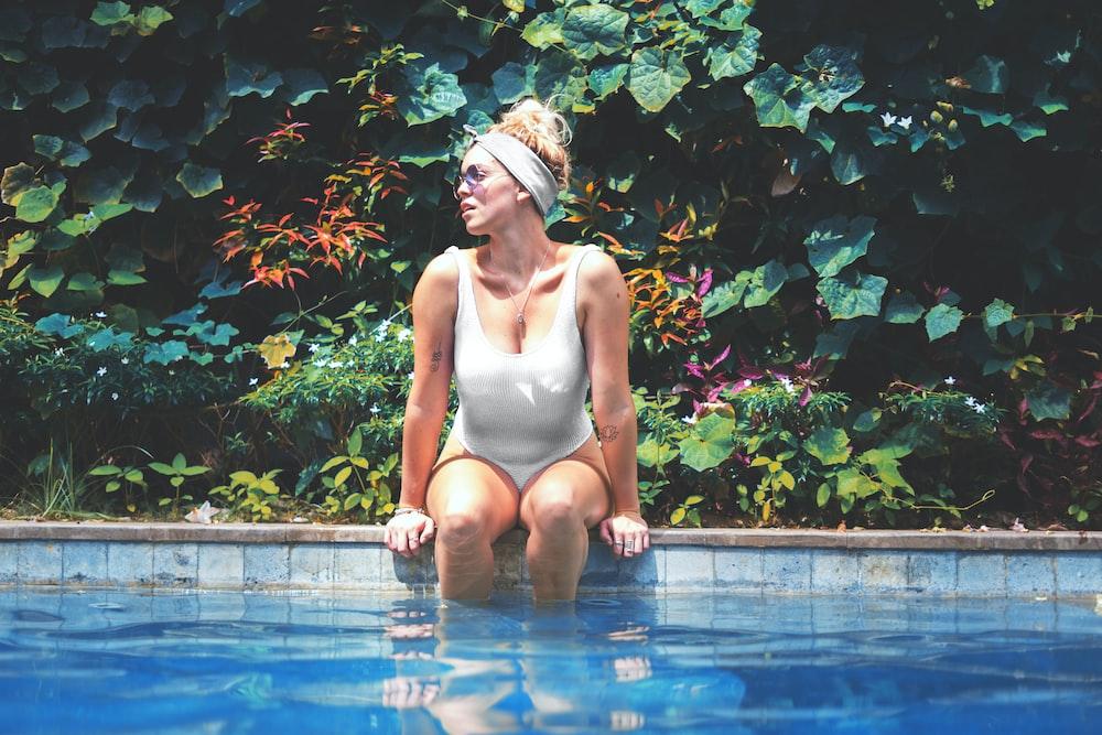woman wearing white one piece bikini sitting on pool