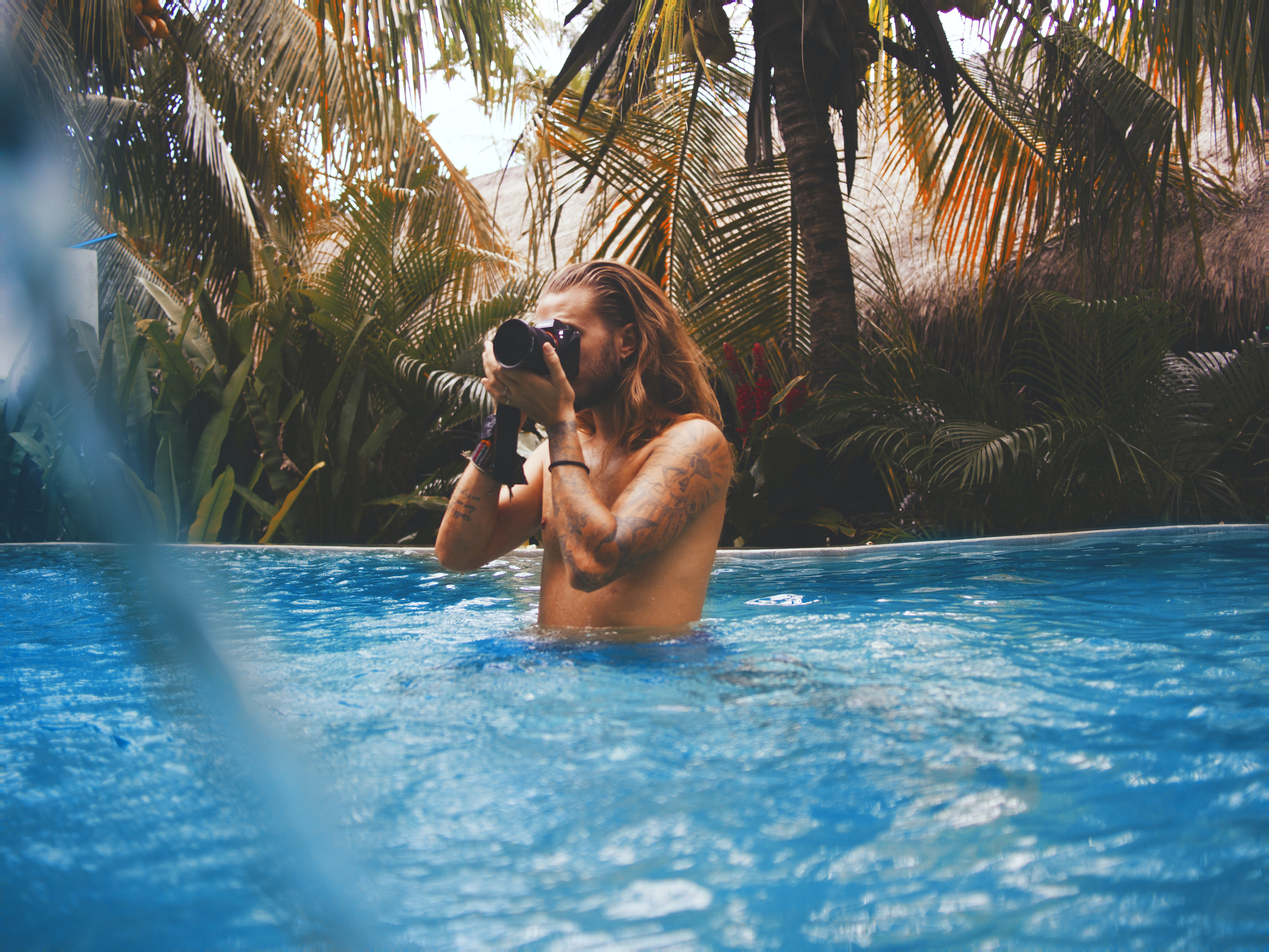man holding camera in swimming pool