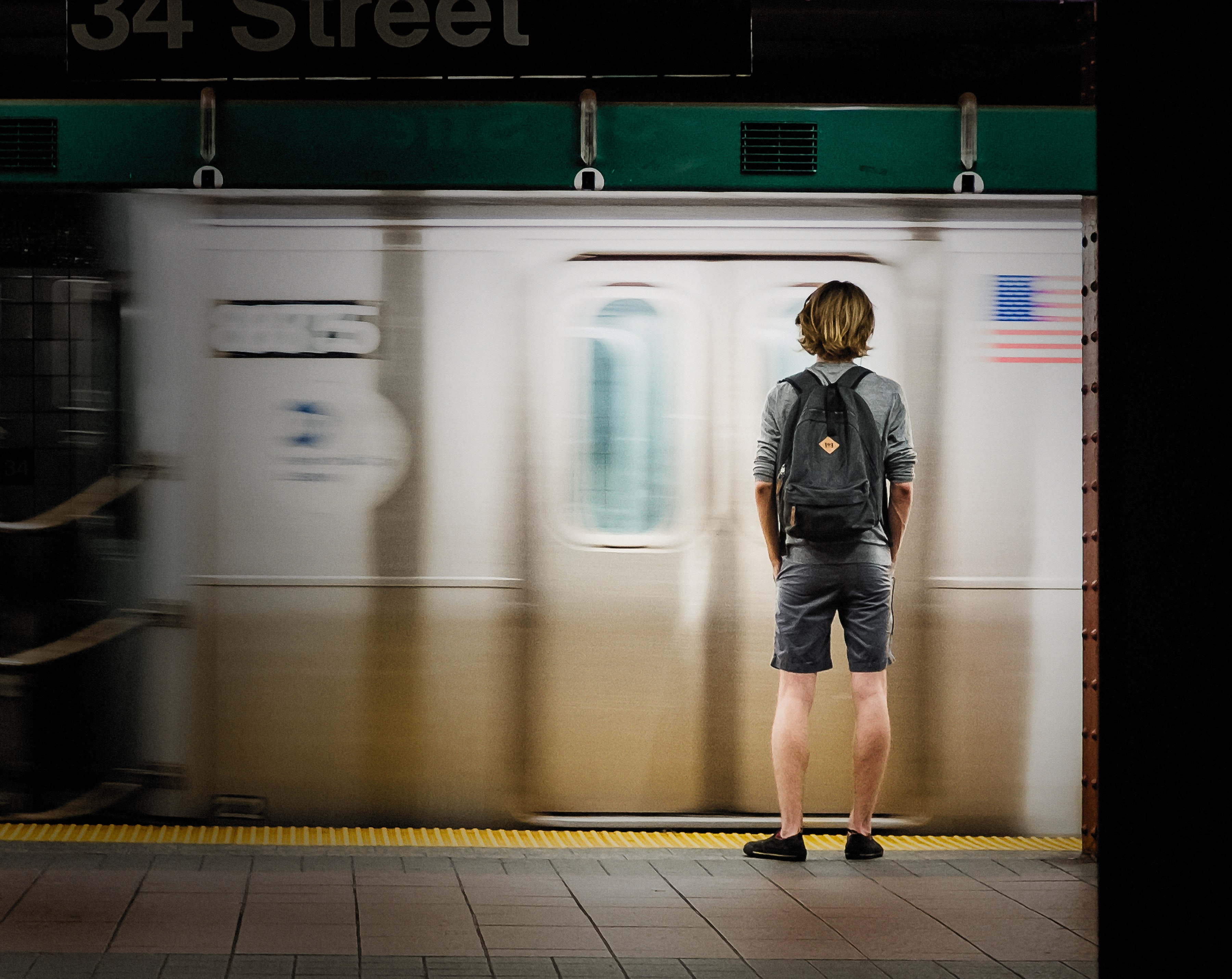 time lapse photography of man standing in front of train