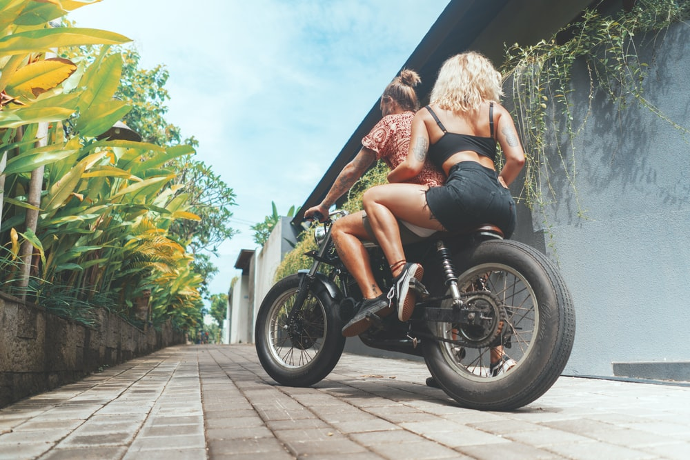 two women riding on black motorcycle during daytime