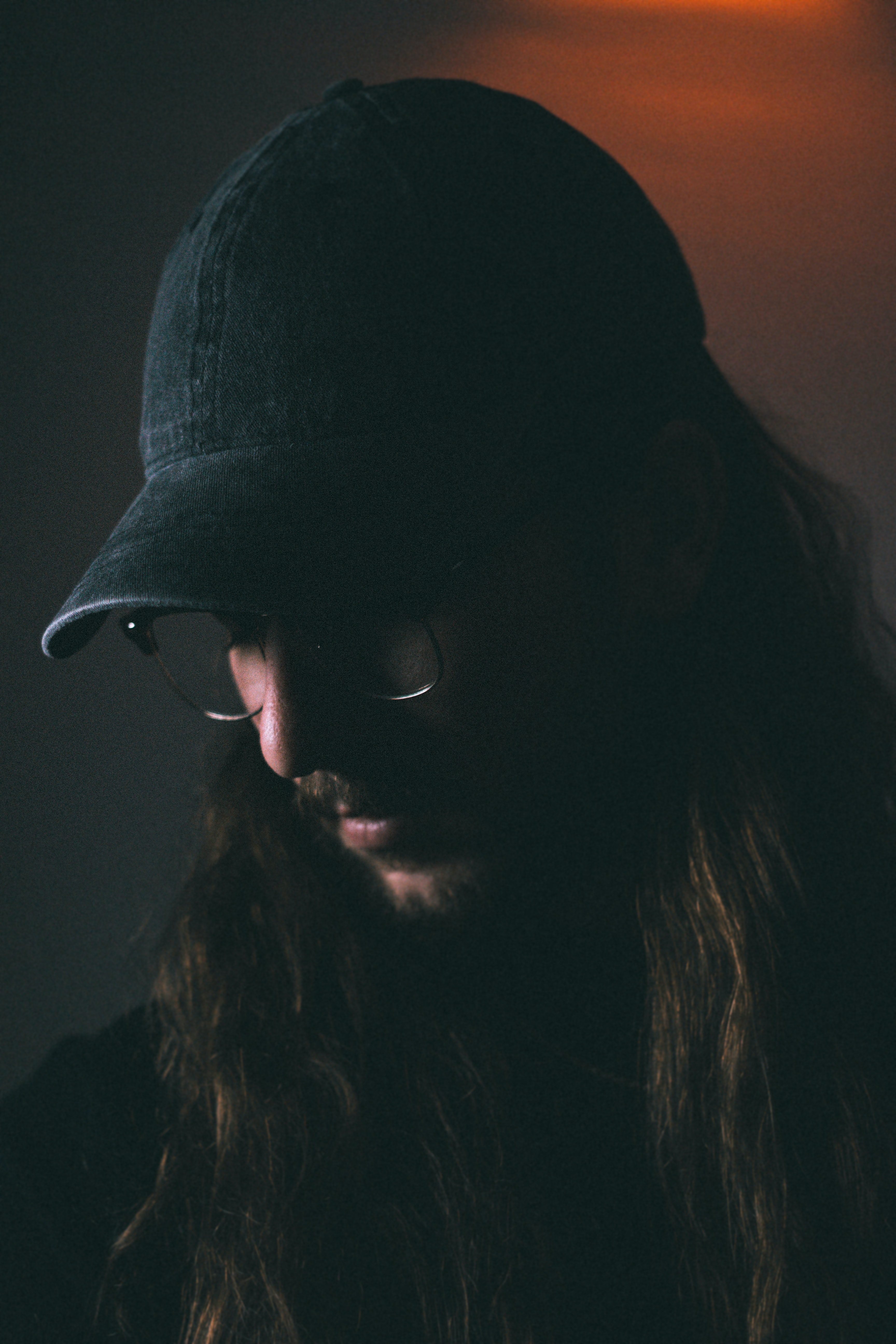 man wearing black fitted cap looking down closeup photography