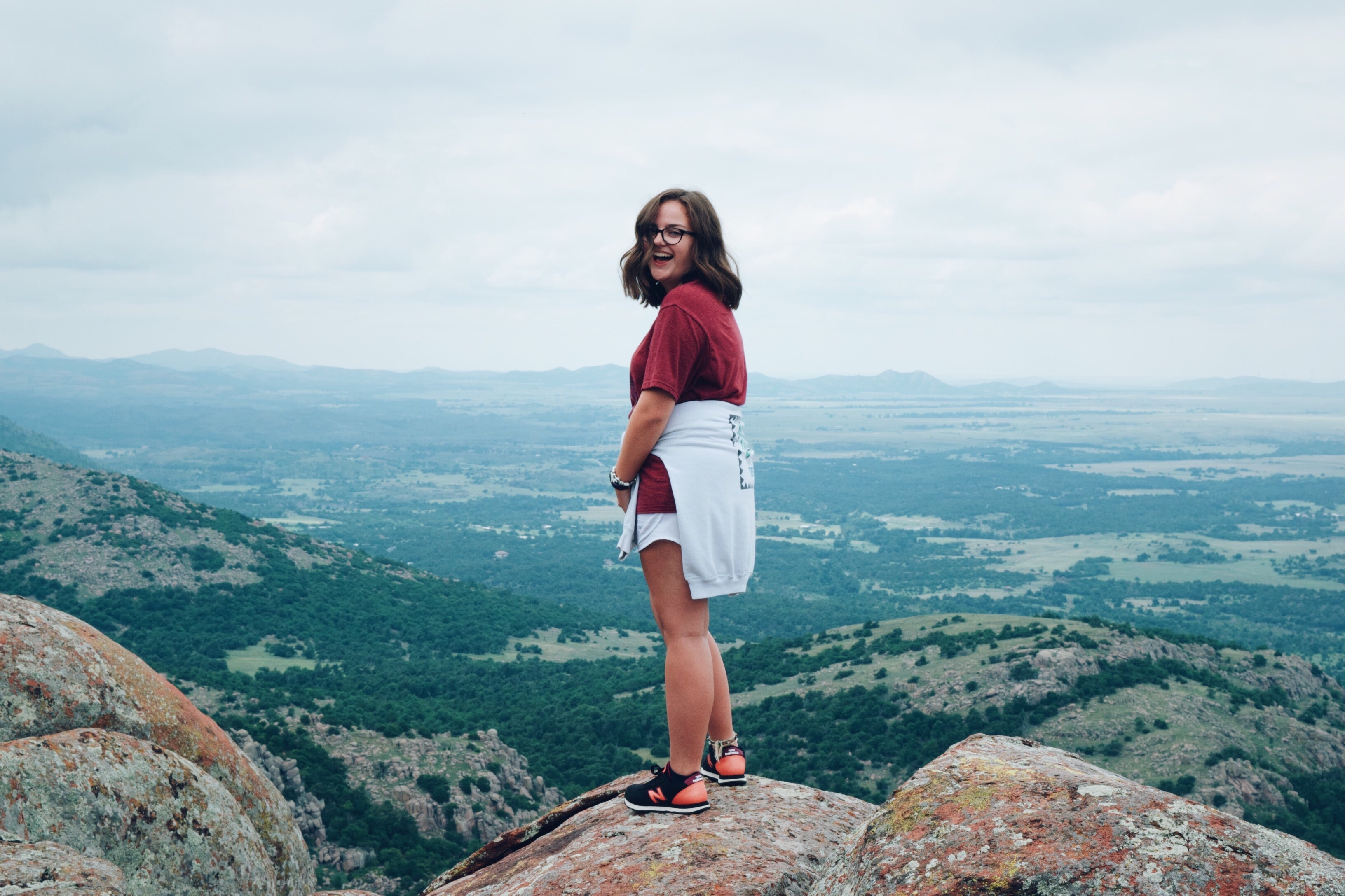 woman in red t-shirt standing on rock during daytime