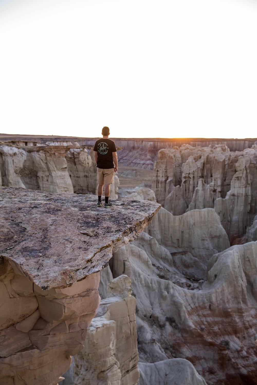 man standing on mountain's edge