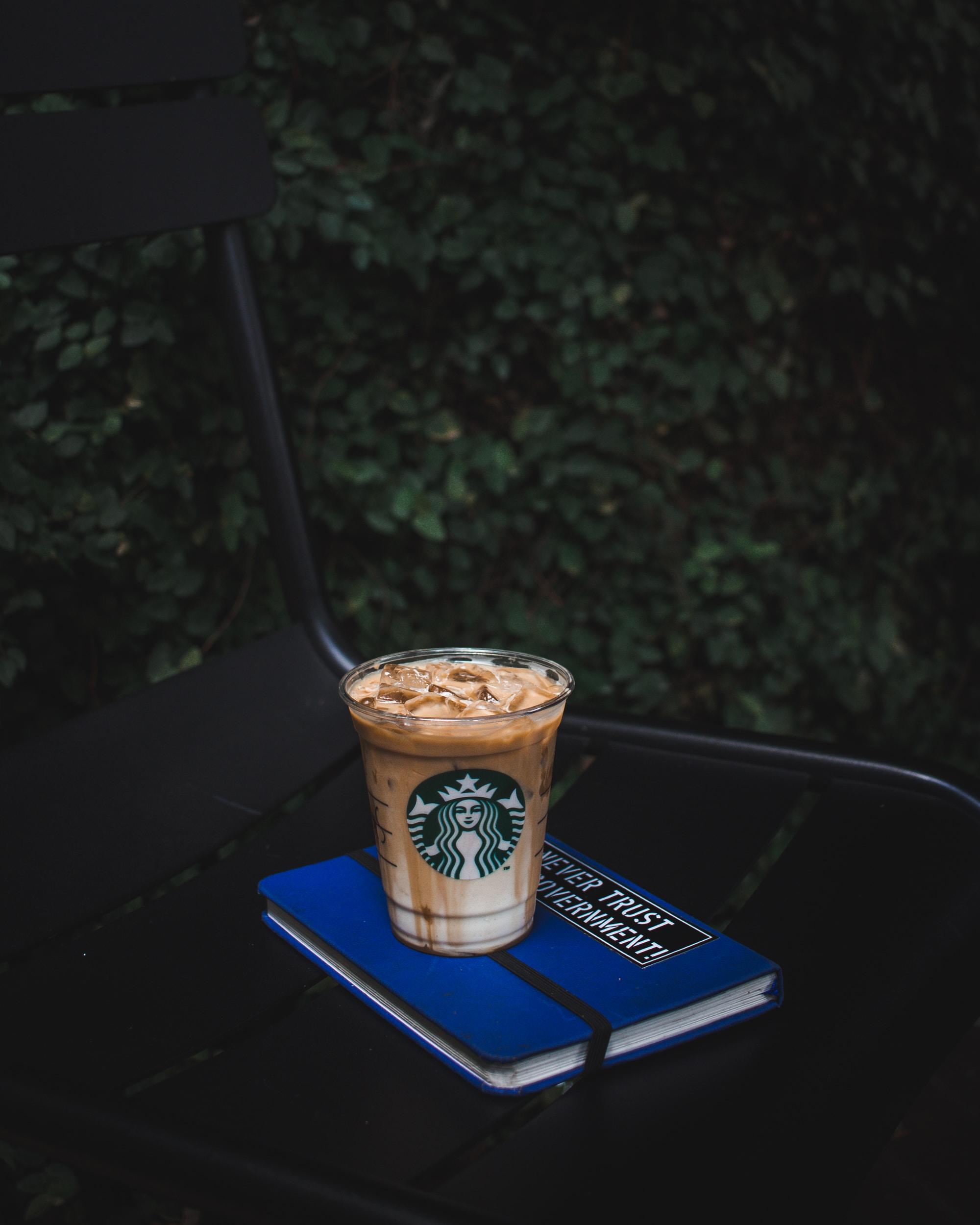 Starbucks plastic cup on blue book