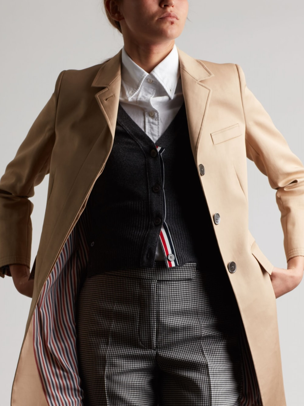 person wearing brown coat while putting hands on packet