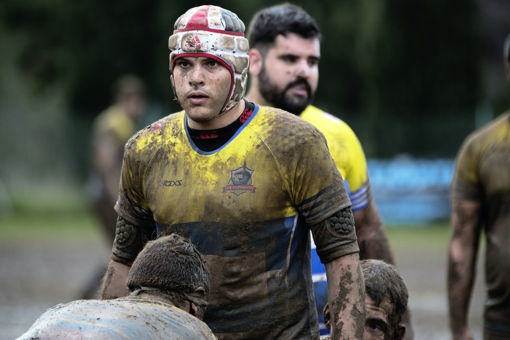 man wearing yellow and blue shirt on mud field during daytime