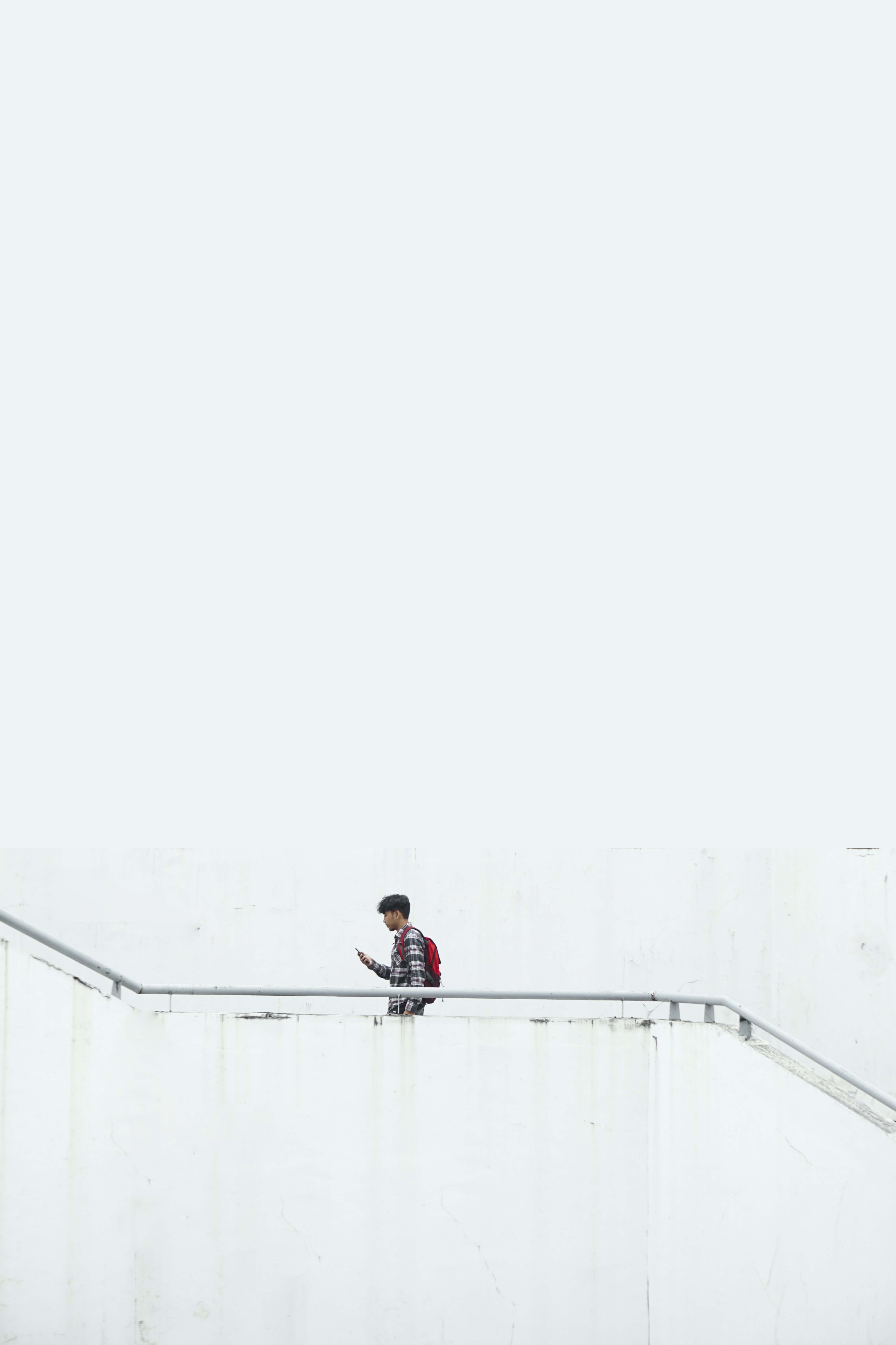 man on stair wearing red backpack