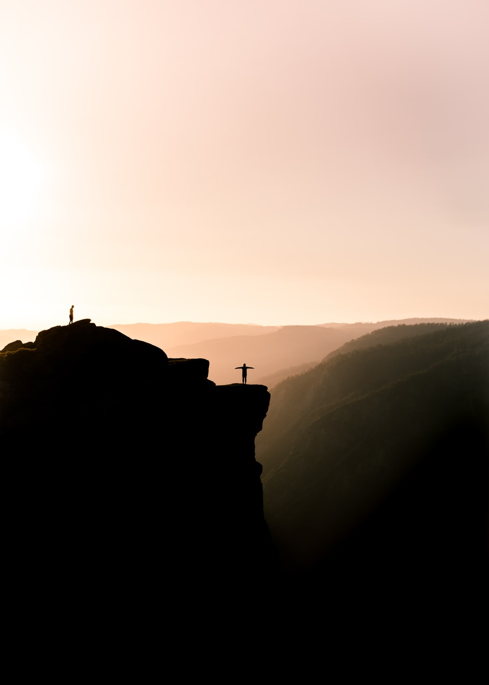 silhouette of person on cliff