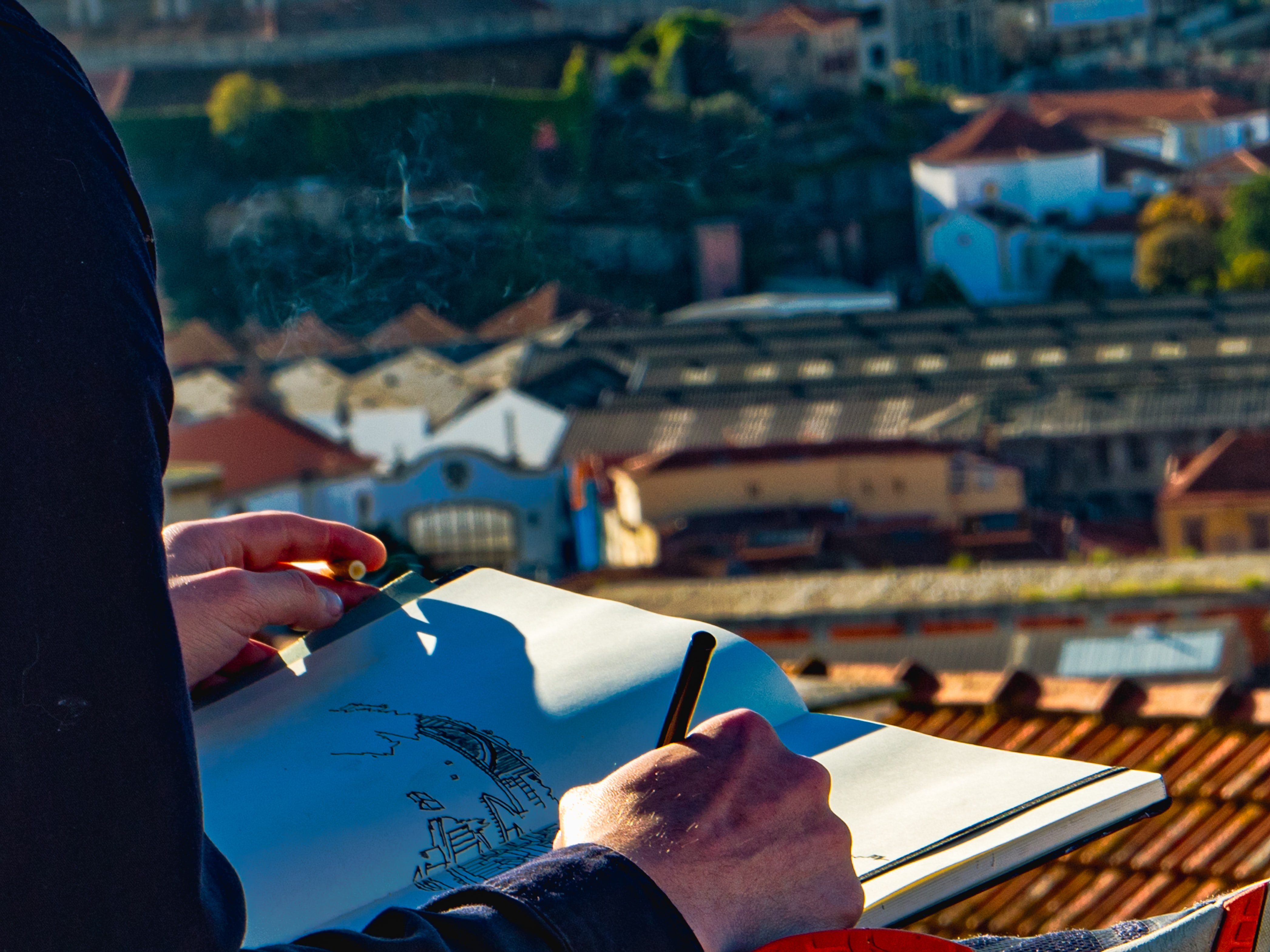 man sketching houses on roof