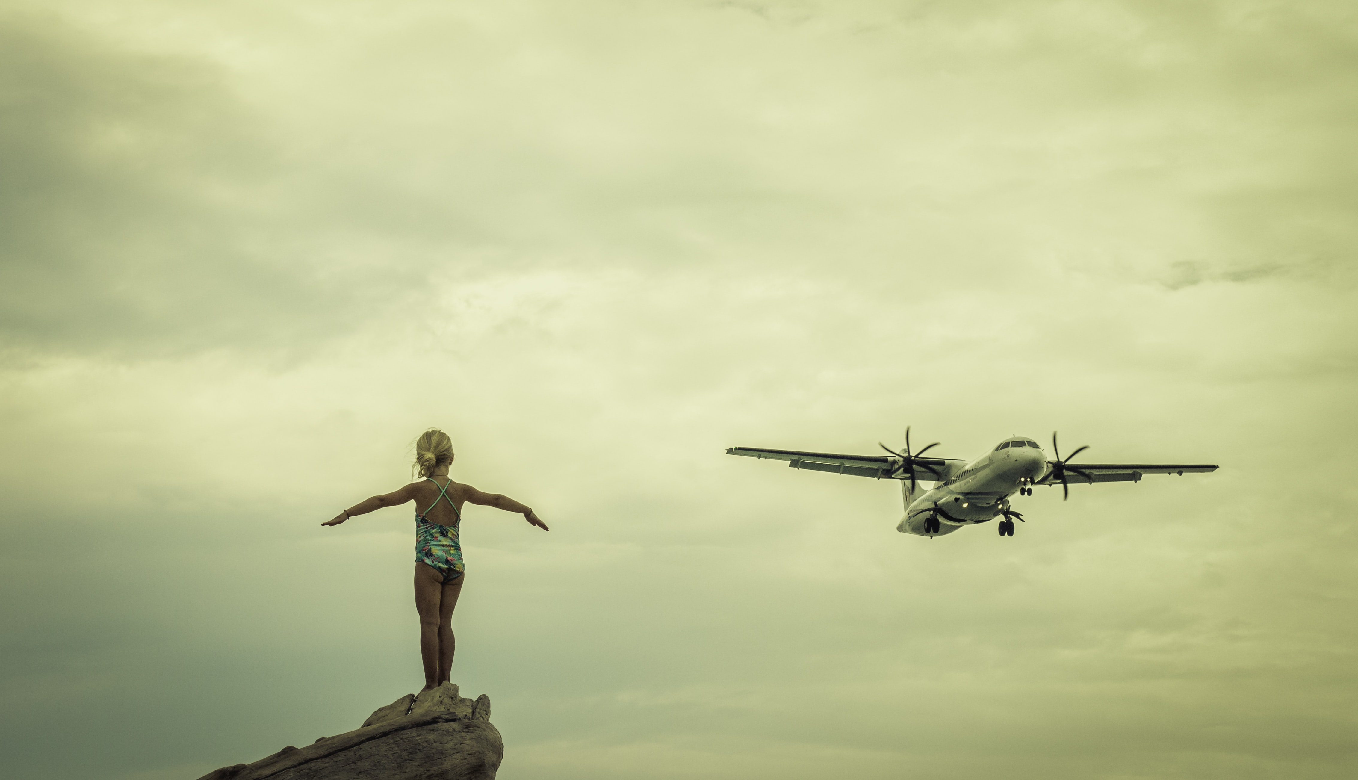 girl standing on cliff under cloudy sky with airplane on flight