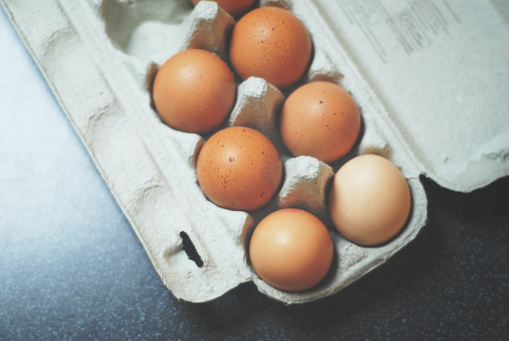 seven brown eggs on tray