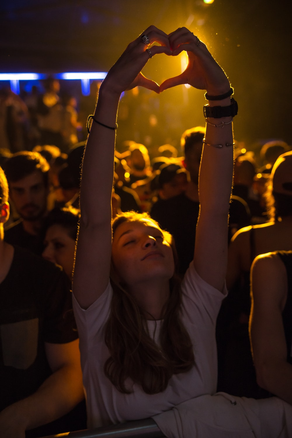 woman at crowd raising her hand while making heart sign