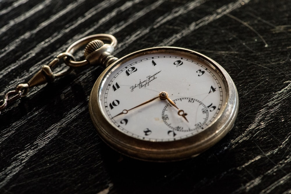 round silver-colored analog pocket watch on table