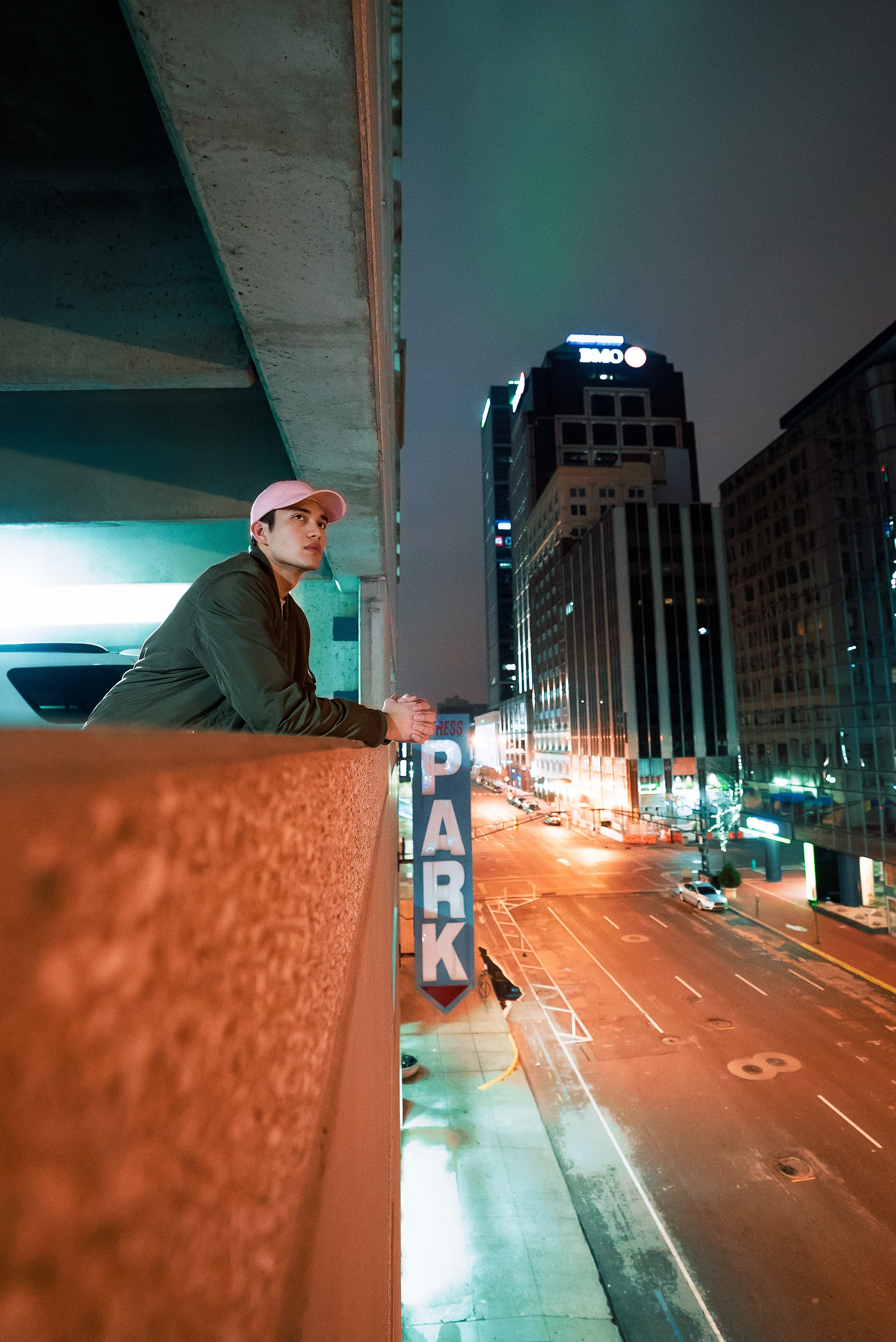 man leaning on concrete railing on building