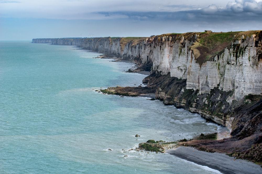 gray cliff near ocean in landscape photography