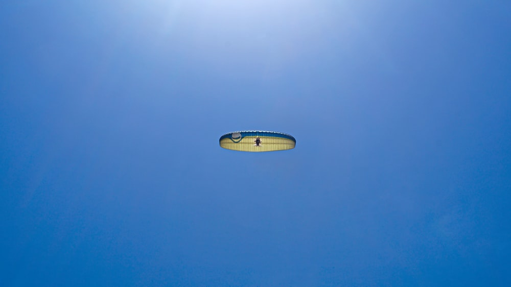 man parachuting with clear sky