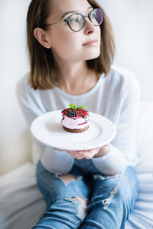 woman wearing white shirt holding plate of cake