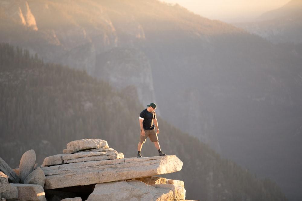man standing on rock cliff near mountain