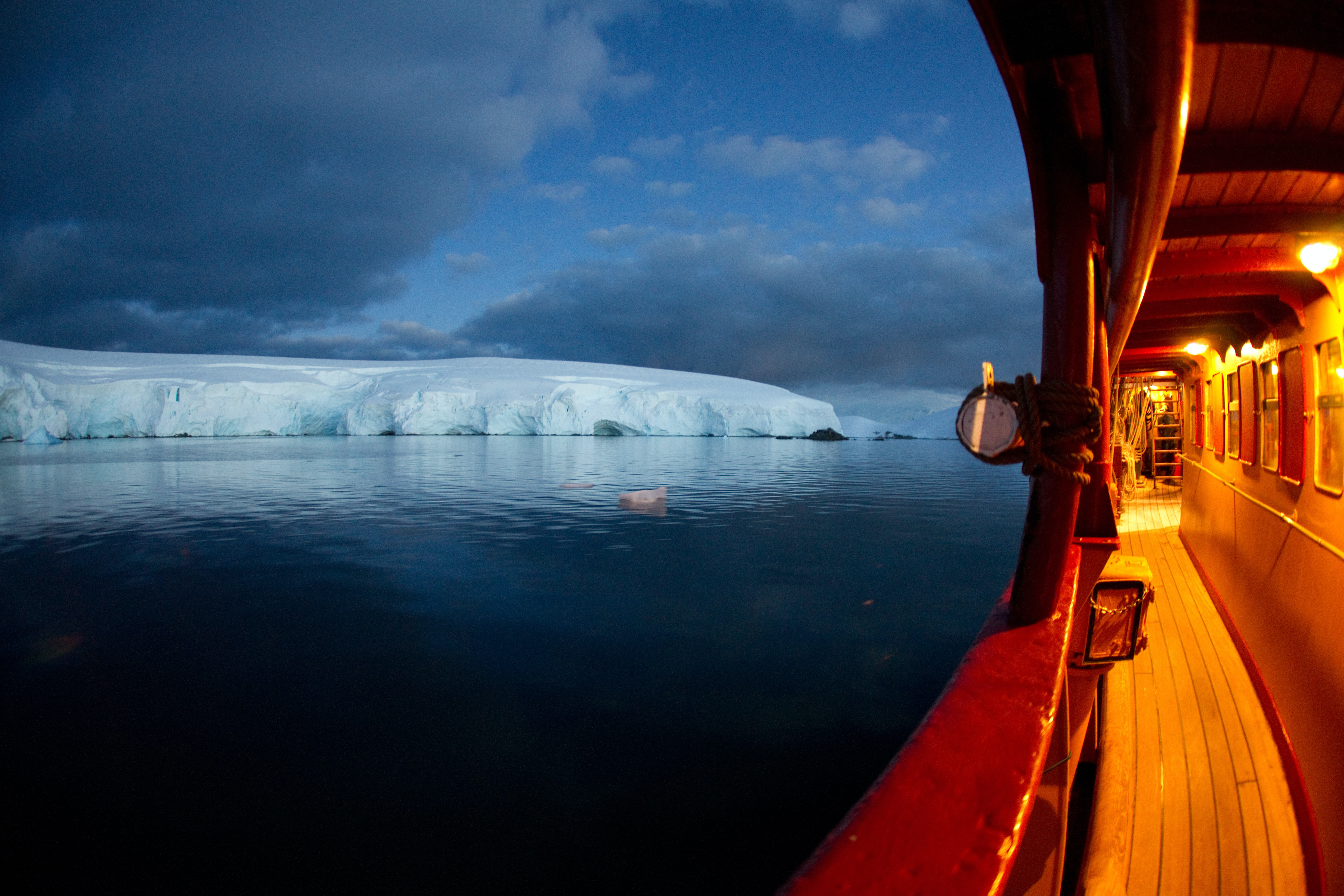 ship floating on ocean heading to ice burg