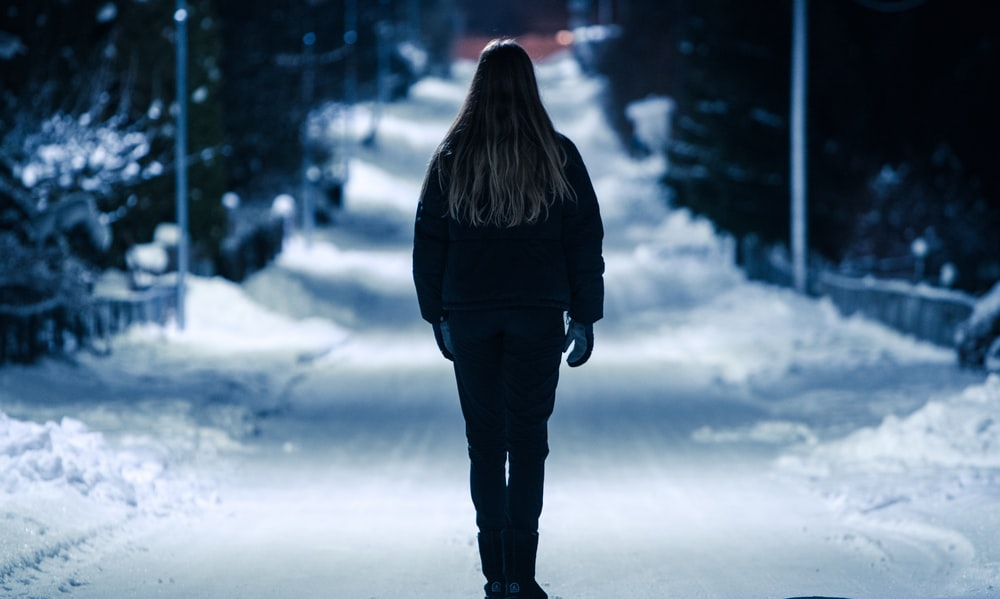 person standing on road with snows