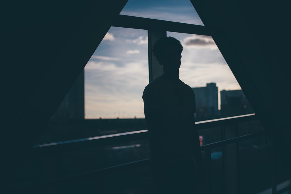 silhouette of man standing beside rails facing glass wall and buildings during blue hour