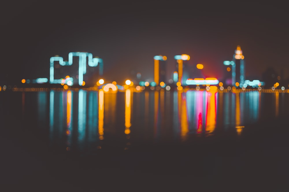 bokeh photography of cityscape on body of water