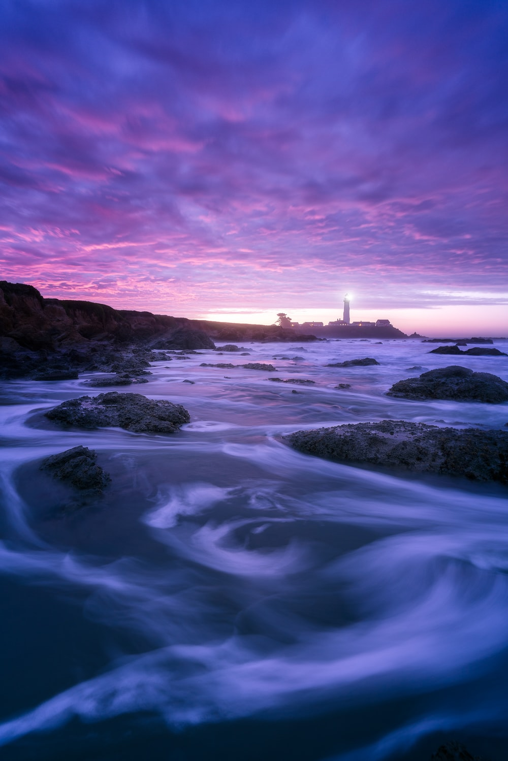 rocks and sea with silhouette of lighthouse in background