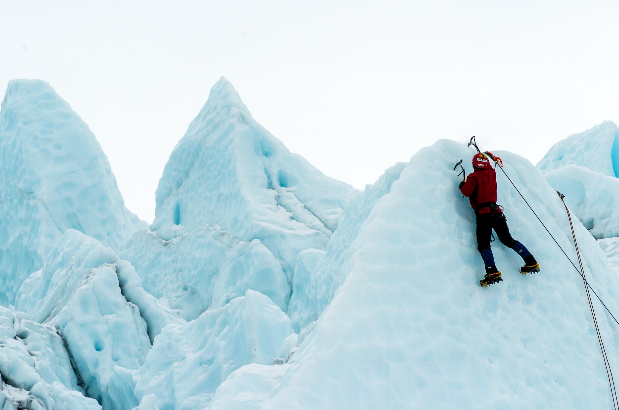 person climbing snowy mountain