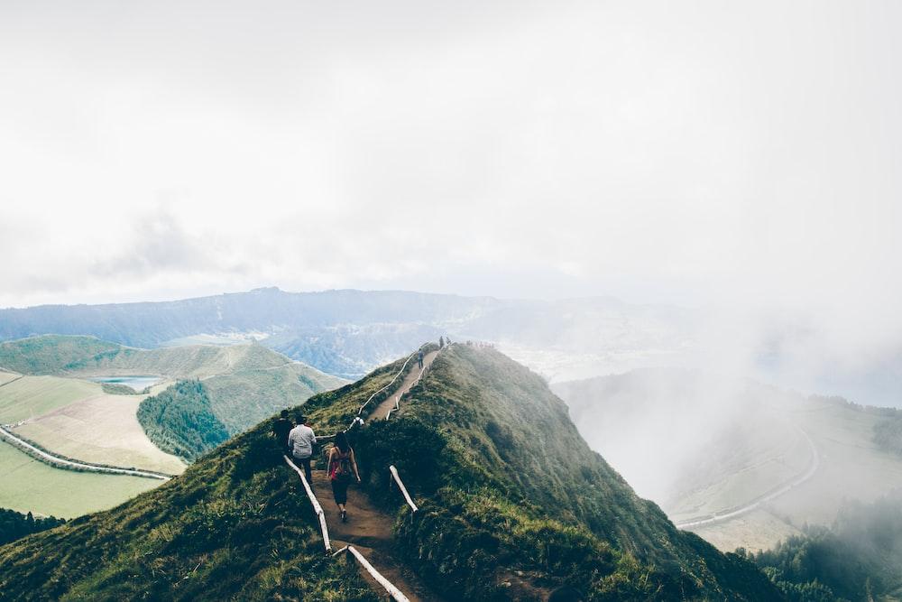 man and woman walking on mountain