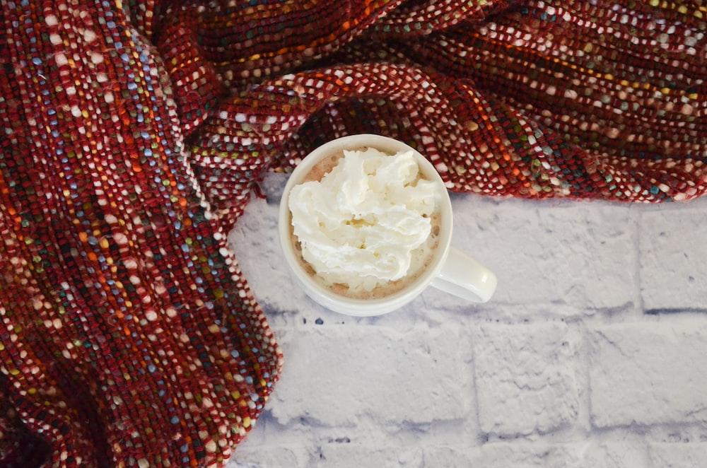 white ceramic mug near red textile