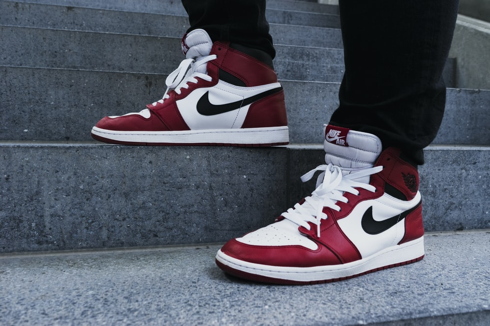person wearing pair of red-and-white Air Jordan 1 shoes
