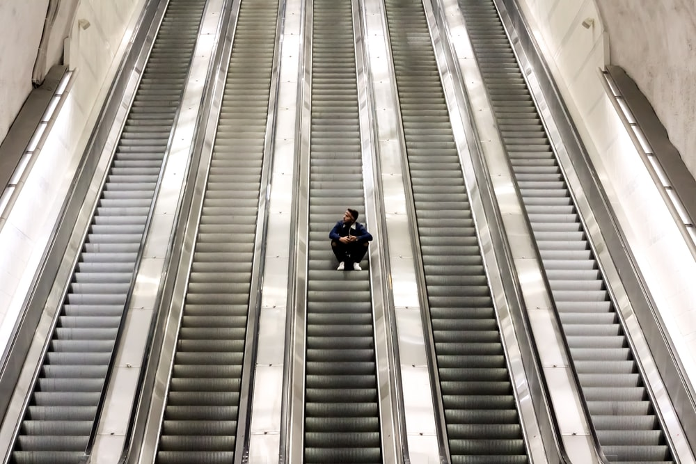 man sitting on escalator