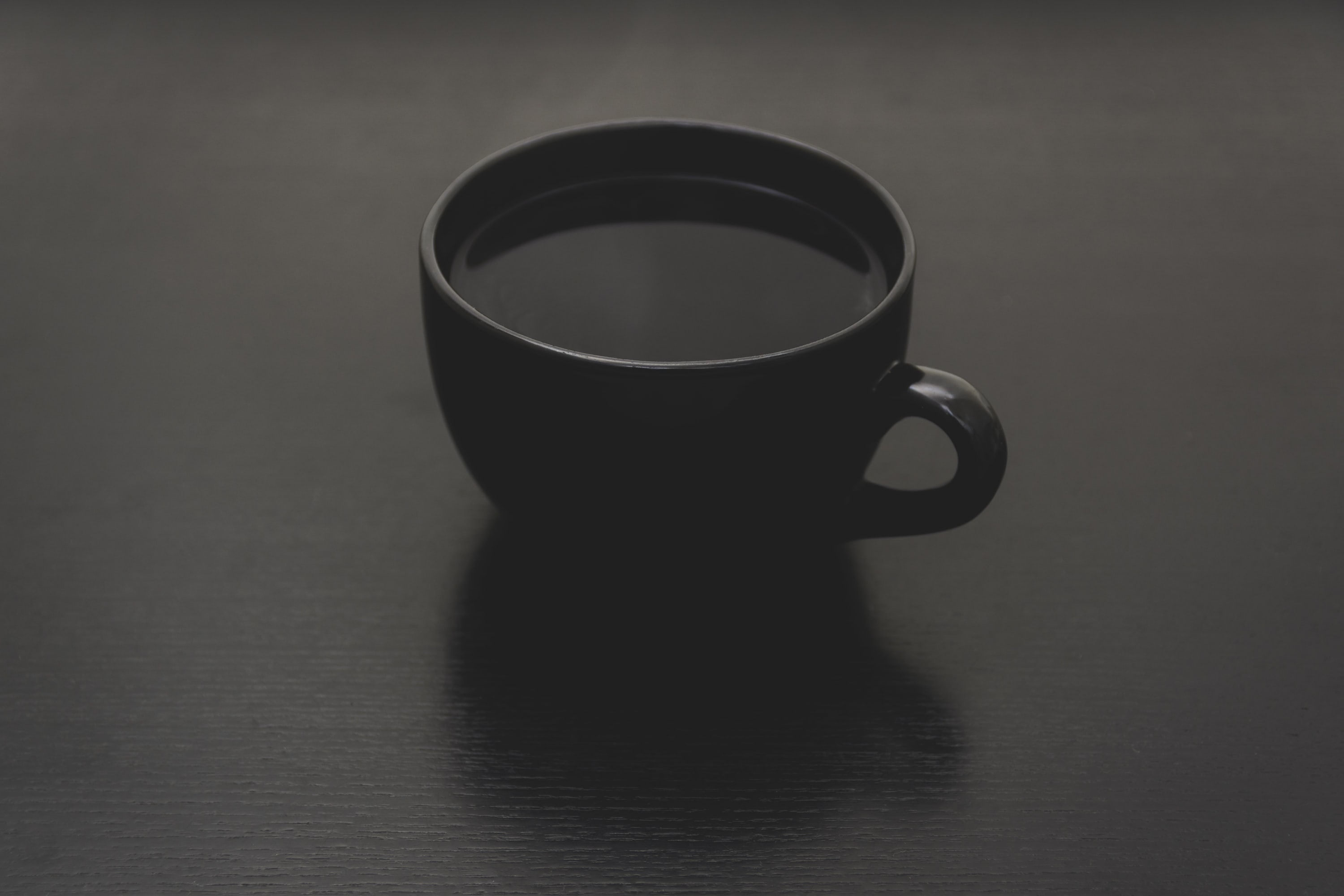 black ceramic mug with liquid close up photo
