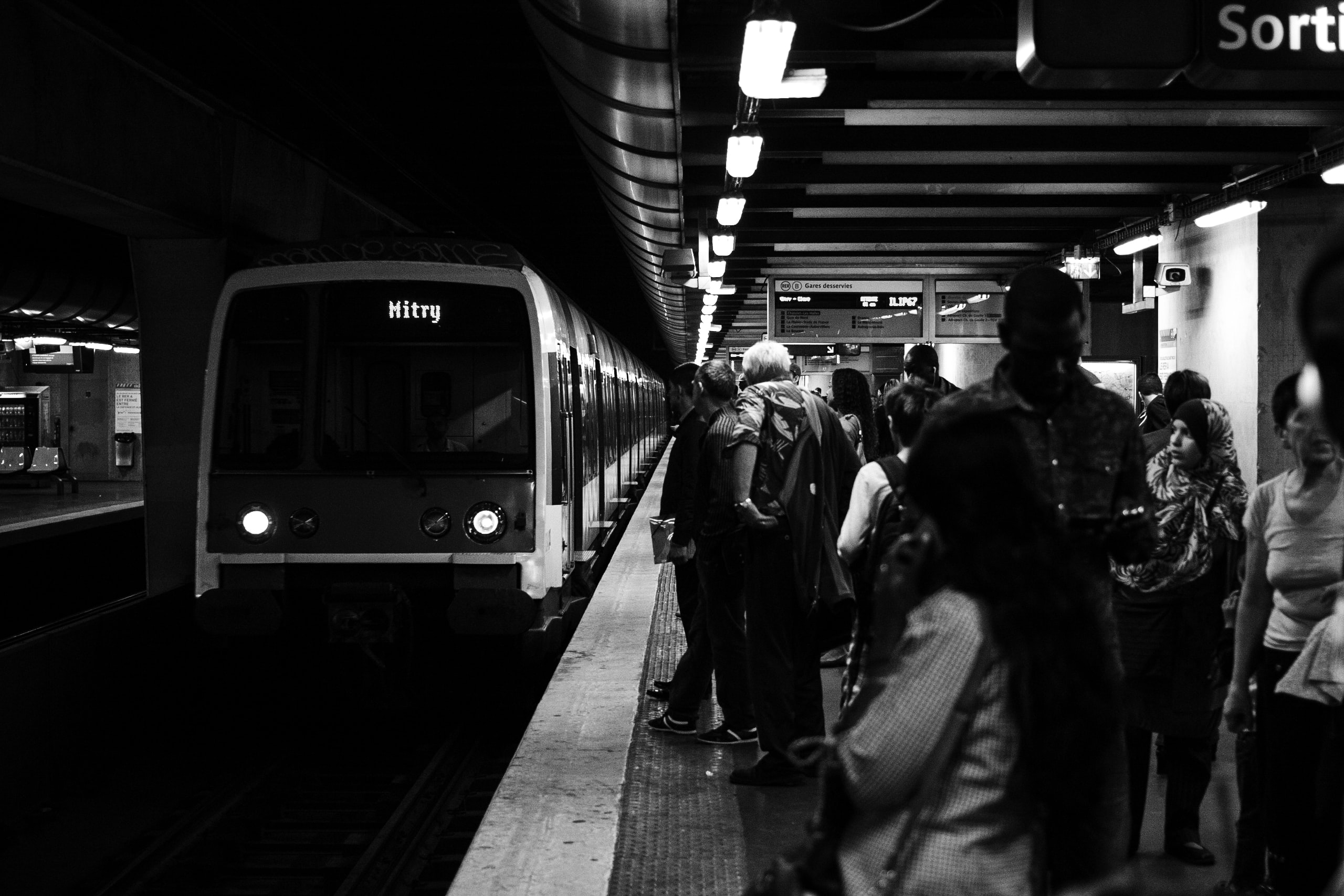 group of people waiting for the train in grayscale photography
