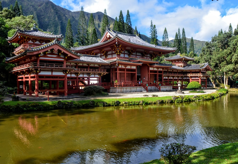 red and white temple near body of water and mountain under cloudy sky