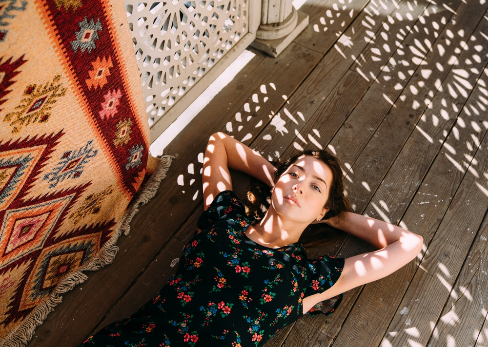 woman lying on brown wooden planks