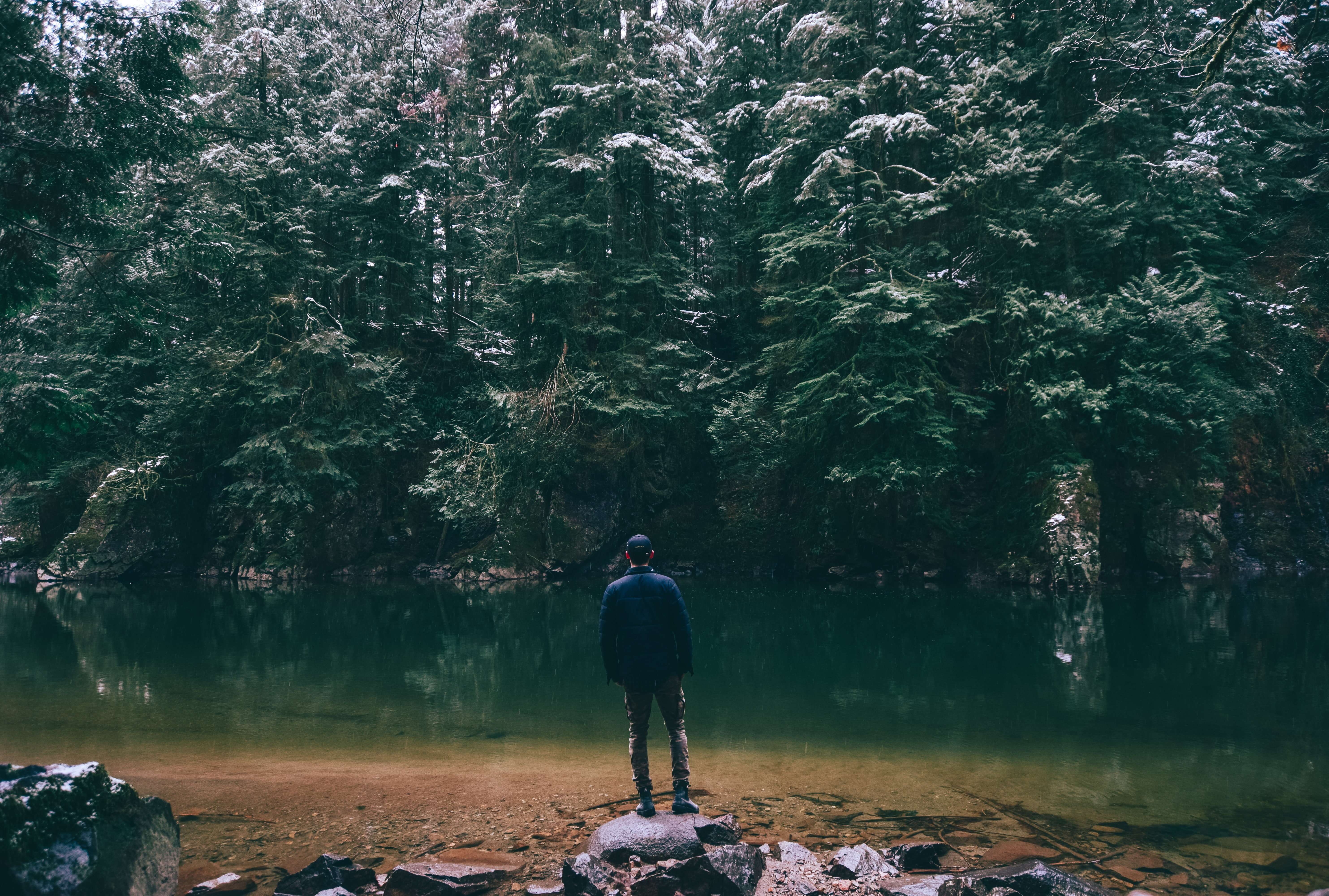 man standing on rock facing body of water surrounded with trees