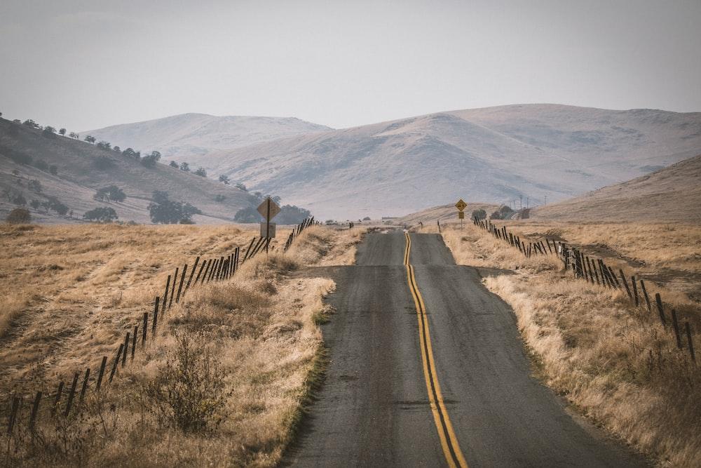 gray concrete road between brown grass field